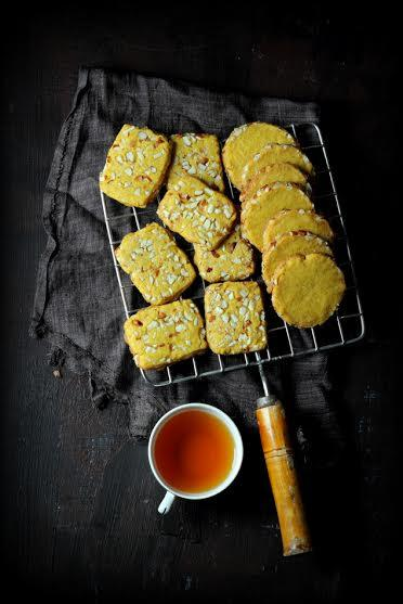 <p><b>Ingredients</b></p><p>Thandai Mix<br /></p><p>¼ cup almonds (lightly toasted).<br />1 tbsp Melon seeds (charmagaz).<br />12 – 14 peppercorns.<br />1 tbsp poppy seeds (white) / poshto / khus khus.<br />1 tbsp fennel seed powder.<br />½ tsp cardamom powder.</p><p>For Cookies</p><p>120 grams butter.<br />½ cup + 2 tbsp caster sugar.<br />1¼ cups maida.<br />¼ cup + 2 tbsp Aata / wholewheat flour.<br />¼ tsp baking powder.<br />A pinch of baking soda / soda bi-carb.<br />¼ tsp saffron.<br />1½ tbsp warm milk (to soak the saffron strands)<br />½ cup Thandai mix.<br />¼ cup finely chopped almonds (optional).</p><p><b>Method</b></p><p>For the Thandai mix, in a spice blender powder the ingredients. Store in a small jar or bottle.</p><p>Crush the saffron and soak it in warm milk for at least an hour to enhance its flavor.</p><p>Whisk together the maida, corn flour, whole meal, baking powder and baking soda for half minute. Mix in the thandai mix and whisk for another half a minute. Set aside.</p><p>In a mixing bowl, whisk together the butter and sugar till light and fluffy. Mix in the saffron milk and then the flour mix. Bring together the butter and flour mix till there are no dry bits. Do not over work with the dough. (You do not need to knead the dough.)</p><p>Roll the dough into a log that is 7 to 7½ inch long. Tightly wrap the rolled dough in a cling film to retain its shape. Store in refrigerator for at least 2 hours (to obtain a hard dough so that it can be easily sliced).</p><p>Preheat the oven at 170 degrees C for five minutes.</p><p>Unwrap the cling film and slice the cookie dough log in half inch thick slices and arrange them on a baking sheet at least half a centimetre gap. Bake the cookies in the preheated oven for 10 – 12 minutes or till the edges begin to turn golden brown.</p><p>Remove the baking sheet from the oven and allow the cookies to cool on the baking sheet for 5 minutes before carefully transferring them on to the wire rack. Cool completely bef