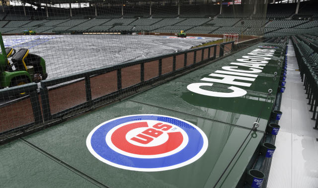 The tarp lays on Wrigley Field after a baseball game between the Atlanta Braves and the Chicago Cubs was postponed on Sunday, April 15, 2018, in Chicago. The game is rescheduled for Monday May 14, 2018. (AP Photo/Matt Marton)