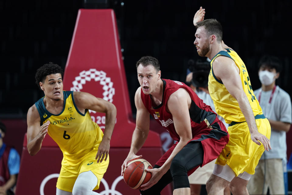 Germany's Johannes Voigtmann, center, passes between Australia's Josh Green, left, and Nic Kay, right, during a men's basketball preliminary round game at the 2020 Summer Olympics, Saturday, July 31, 2021, in Saitama, Japan. (AP Photo/Charlie Neibergall)