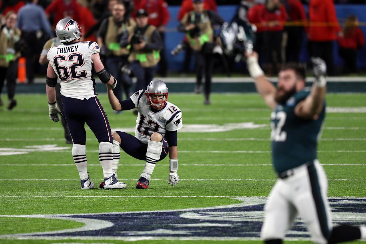 <p>New England Patriots offensive guard Joe Thuney (62) helps quarterback Tom Brady (12) up after losing to the Philadelphia Eagles in Super Bowl LII at U.S. Bank Stadium. Mandatory Credit: Brace Hemmelgarn-USA TODAY Sports </p>