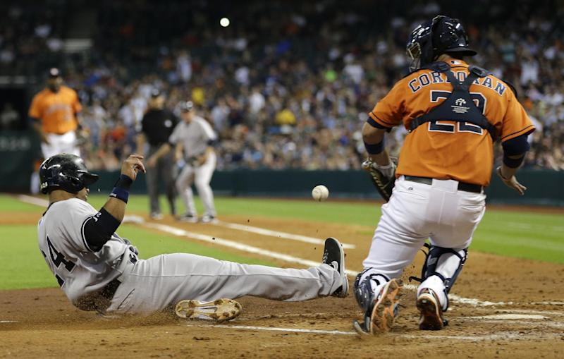 New York Yankees' Robinson Cano, left, slides safely across home plate to score as Houston Astros catcher Carlos Corporan (22) waits for the ball during the fourth inning of a baseball game on Friday, Sept. 27, 2013, in Houston. (AP Photo/David J. Phillip)