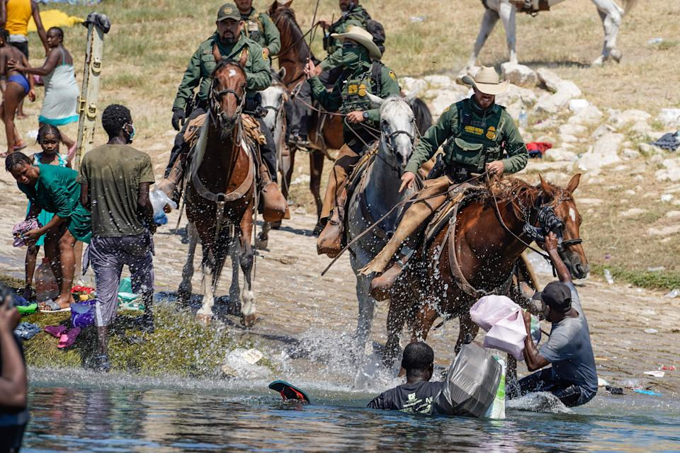 U.S. Customs and Border Patrol agents on horseback try to stop Haitian migrants from entering an encampment on the banks of the Rio Grande in Del Rio, Texas, on Sept. 19, 2021.