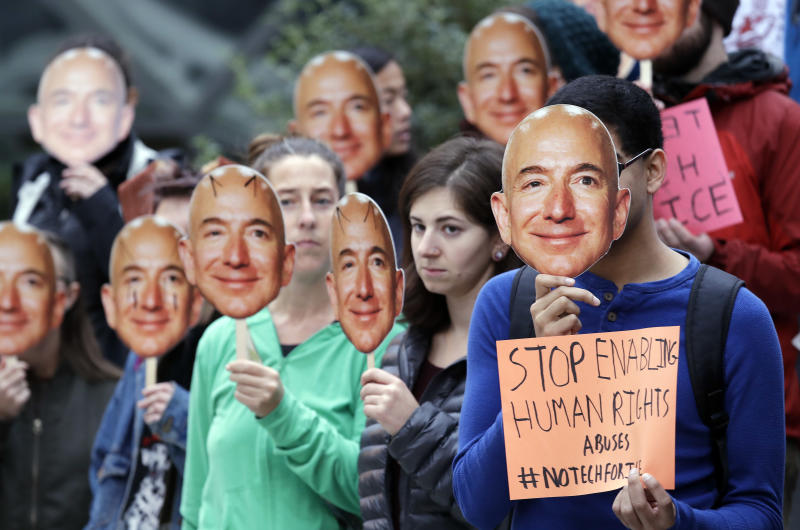 "Demonstrators hold images of Amazon CEO Jeff Bezos near their faces during a Halloween-themed protest at Amazon headquarters over the company's facial recognition system, ""Rekognition,"" Wednesday, Oct. 31, 2018, in Seattle. Protesters said that they were there in support of hundreds of Amazon employees who have signed a letter asking the company to stop marketing their facial recognition software to ICE and to drop its contract with software company Palantir and to law enforcement agencies. (AP Photo/Elaine Thompson)"