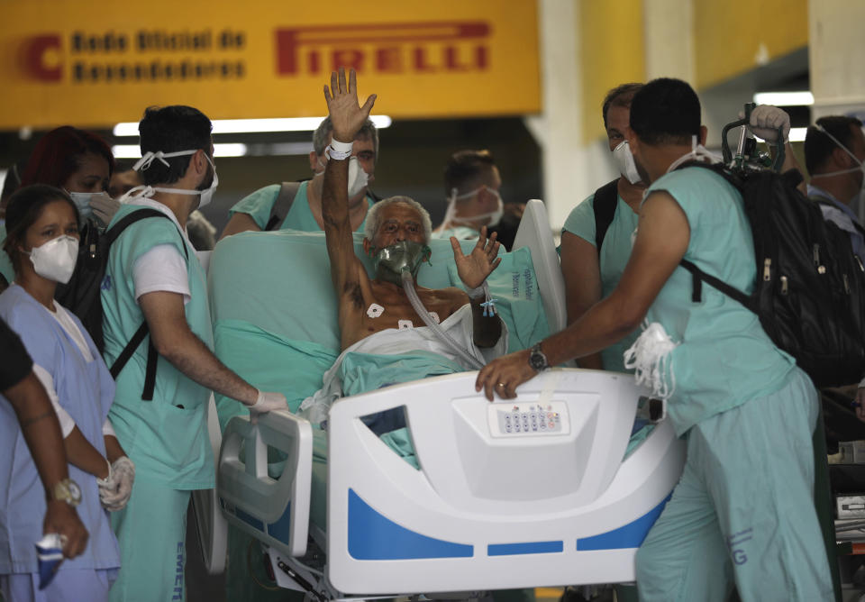 A patient waves as he is successfully evacuated from the Bonsucesso Federal Hospital while firefighters douse a blaze in Rio de Janeiro, Brazil, Tuesday, Oct. 27, 2020. According to the hospital, a 42-year-old female COVID-19 patient, who was in critical condition, died while she was being evacuated. (AP Photo/Silvia Izquierdo)