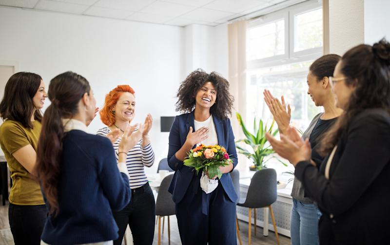 Pictured: Smiling woman with flowers laughs as colleagues applaud her promotion. Image: Getty