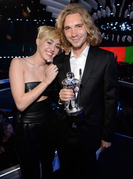 """<p>A year after Twerkgate, Miley returned to the VMAs to accept a Video of the Year award for """"Wrecking Ball"""" and tried to class things up, using her time in the spotlight to draw awareness to an important issue: teen homelessness. Miley didn't even give a speech, instead sitting on the edge of the stage in tears (real tears, not """"Wrecking Ball""""-video tears) while her date, a young homeless man named Jesse Helt, accepted the award on her behalf. Unfortunately, Miley was still unable to entirely avoid controversy, when it was revealed that Helt had a criminal past; his TV appearance prompted police to send out a warrant for his arrest for probation violation, and he was later sentenced to six months in jail. (Source: Getty Images) </p>"""