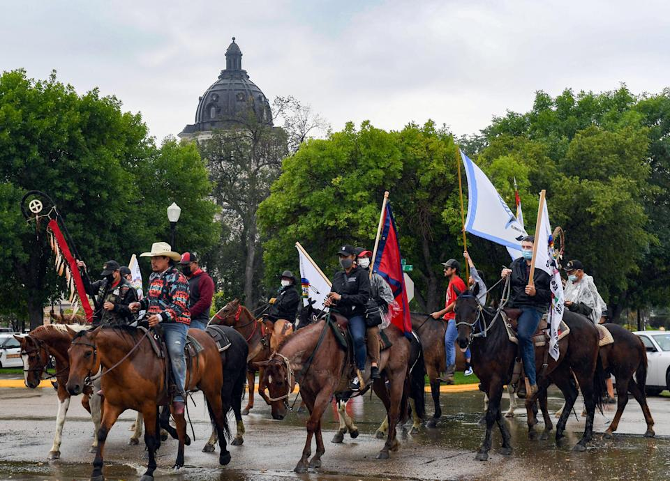Horse riders pass in front of the South Dakota capitol building during a demonstration through the streets of Pierre after the final draft of the state's proposed social studies standards left out multiple specific references to the Oceti Sakowin on Monday, September 13, 2021.