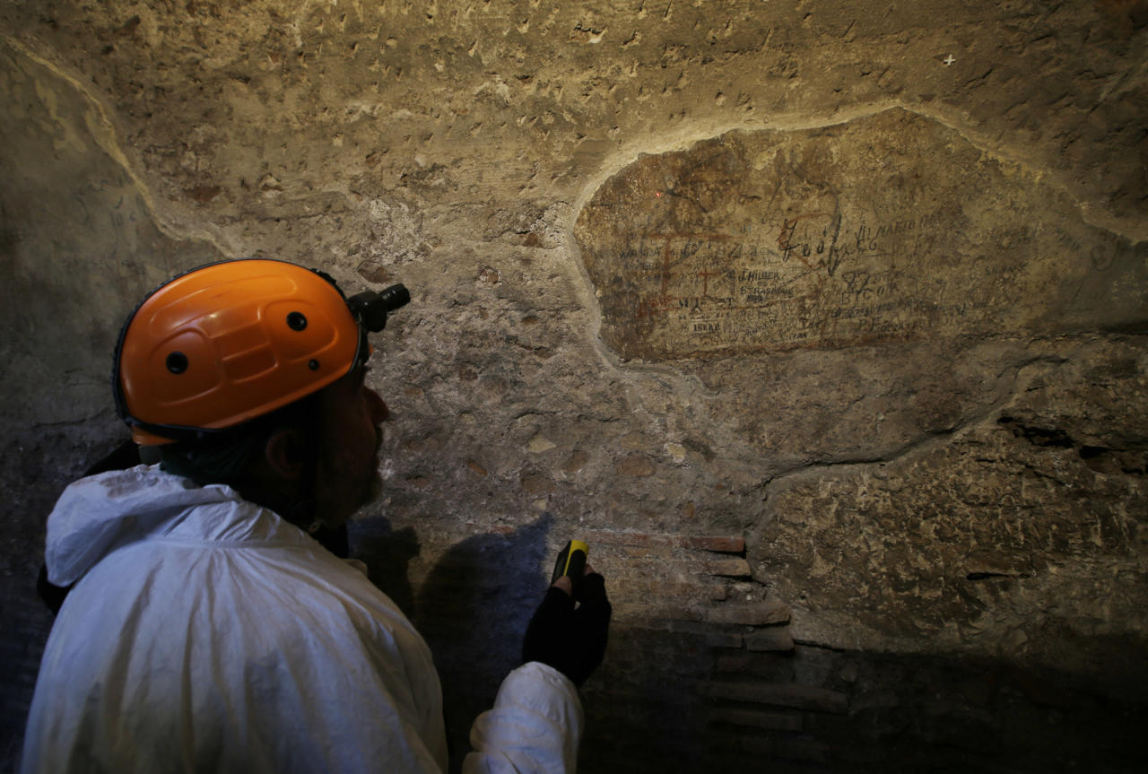 A restorer shows journalists an ancient graffiti recently discovered inside a gallery of Rome's Colosseum, Friday, Jan. 18, 2013. A long-delayed restoration of the Colosseum's only intact internal passageway has yielded ancient traces of red, black and blue frescoes — as well as graffiti and drawings of phallic symbols — indicating that the arena where gladiators fought was far more colorful than previously thought. Officials unveiled the discoveries Friday and said the passageway would be open to the public starting this summer, after the €80,000 ($100,000) restoration is completed. The frescoes were hidden under decades of calcified rock and grime, and were revealed after the surfaces were cleaned. The traces confirmed that while the Colosseum today is a fairly monochrome gray travertine rock, red brick and bits of moss-covered marble, in its day its interior halls were a rich and expensive Technicolor. (AP Photo/Gregorio Borgia)