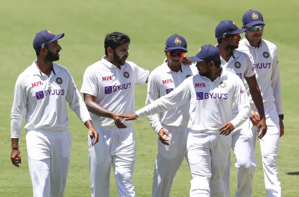 India's Shardul Thakur, second left, is congratulated by teammate Rishabh Pant after taking the wicket of Australia's Tim Paine during play on day two of the fourth cricket test between India and Australia at the Gabba, Brisbane, Australia, Saturday, Jan. 16, 2021. (AP Photo/Tertius Pickard)