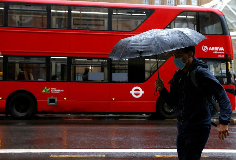 FILE PHOTO: A man with an umbrella walks past a bus in the City of London financial district during the morning rush hour