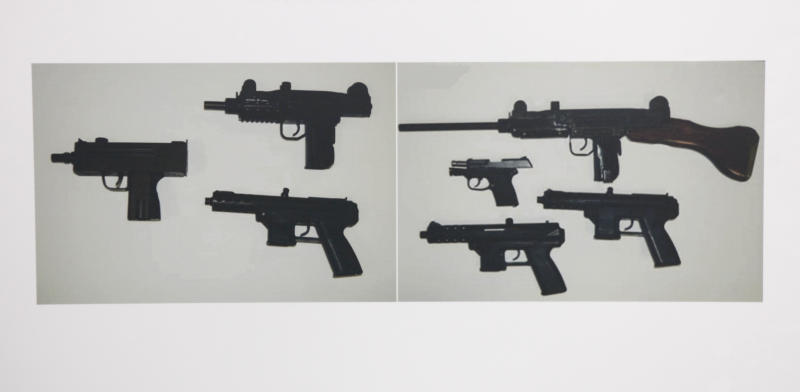 Photographs showing some of guns confiscated during the investigation of alleged illegal gun sales by two Sacramento County Sheriff's deputies are seen at a news conference in Sacramento, Calif., Friday June 1, 2012. Deputies Ryan McGowan, 31, and Thomas Lu, 42, face charges of trafficking in guns that cannot be legally bought by citizens in California.(AP Photo/Rich Pedroncelli)