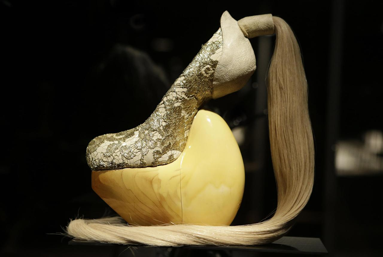 "This Feb. 11, 2013 photo shows a shoe, designed by Masaya Kushino, and made with lacquered Japanese cypress wood, human hair, and lace, displayed at the ""Shoe Obsession"" exhibit at The Museum at the Fashion Institute of Technology Museum in New York. The exhibition, showing off 153 specimens, runs through April 13. (AP Photo/Kathy Willens)"