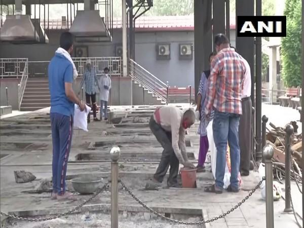 A worker collecting ashes at Nigambodh Ghat crematorium (Photo/ANI)