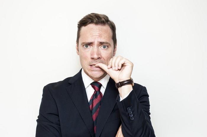 A man in a suit looking nervous, biting his thumbnail.