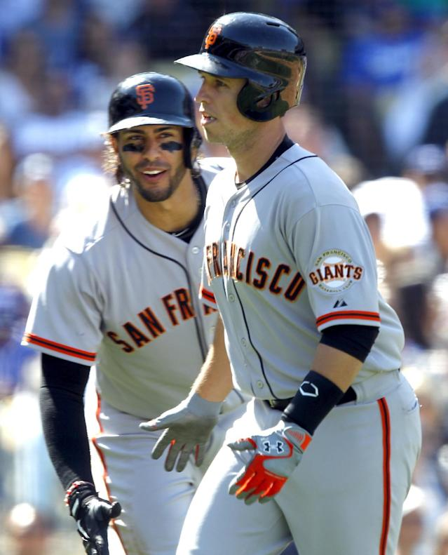 San Francisco Giants' Michael Morse, left, congratulates teammate Buster Posey for hitting a solo home run against the Los Angeles Dodgers in the fifth inning of a baseball game on Saturday, April 5, 2014, in Los Angeles. (AP Photo/Alex Gallardo)