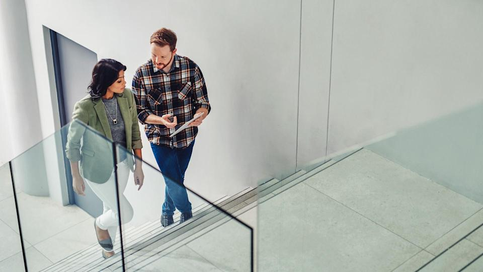 Shot of two young coworkers using a digital tablet while walking up stairs in a modern office.