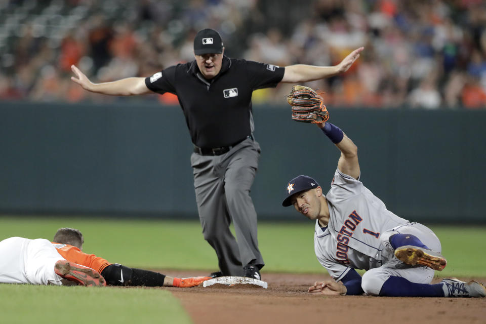 Houston Astros shortstop Carlos Correa, right, holds up the ball with his glove as Baltimore Orioles' Chris Davis keeps a hand on second base after a double, while umpire Mike Everitt makes the call during the sixth inning of a baseball game Saturday, Aug. 10, 2019, in Baltimore. (AP Photo/Julio Cortez)