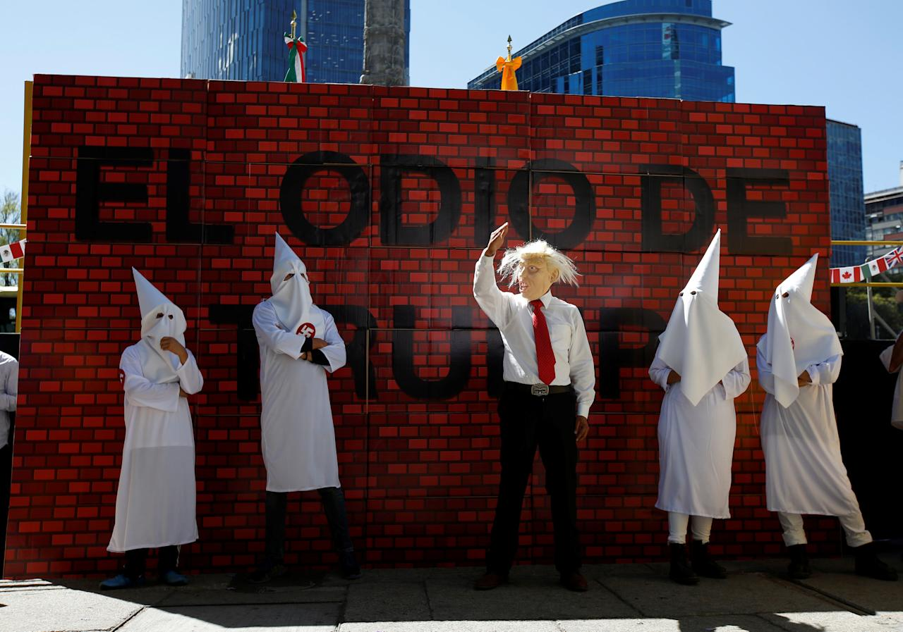 """Actors impersonating U.S. President Donald Trump and members of the Ku Klux Klan stage a performance on behalf of a local Mexican political party during a protest against Trump, in Mexico City, Mexico February 20, 2017. The writing on the mock wall reads """"The hatred of Trump"""". REUTERS/Jose Luis Gonzalez"""
