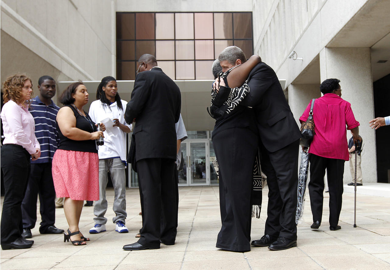 U.S. Attorney Jim Letten hugs a supporter of victims who were shot by New Orleans police, outside Federal Court after sentences were handed down in the case in New Orleans, Wednesday, April 4, 2012. Five former New Orleans police officers were sentenced Wednesday to prison terms ranging from six to 65 years for their roles in deadly shootings of unarmed residents in the chaotic days after Hurricane Katrina. (AP Photo/Gerald Herbert)