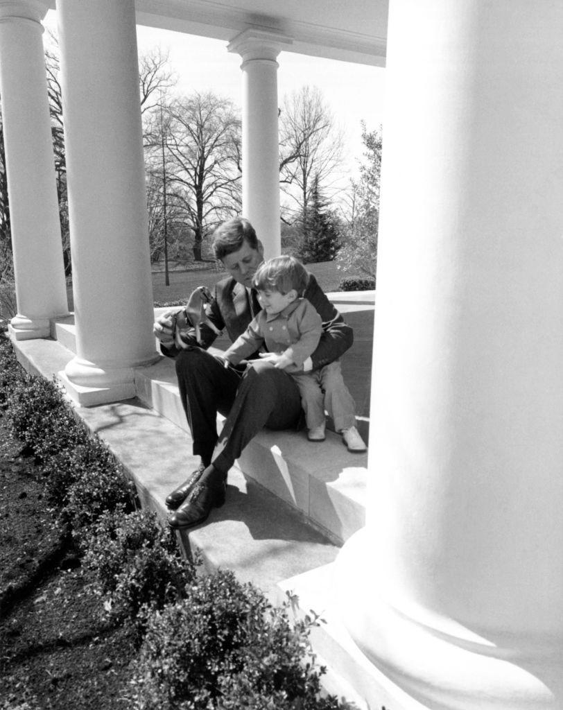 <p>President John F. Kennedy takes a break from his busy schedule to play with his son, JFK Jr., on a wing of the White House in 1962. </p>