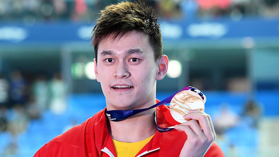 Shown here, Chinese swimmer Sun Yang poses with a gold medal around his neck.