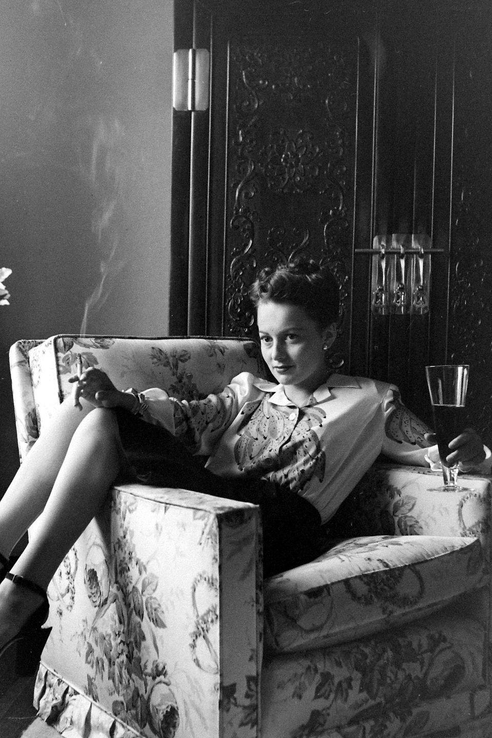 <p>Cigarette lit and a drink in hand, the actress lounges on a sofa in her home. </p>