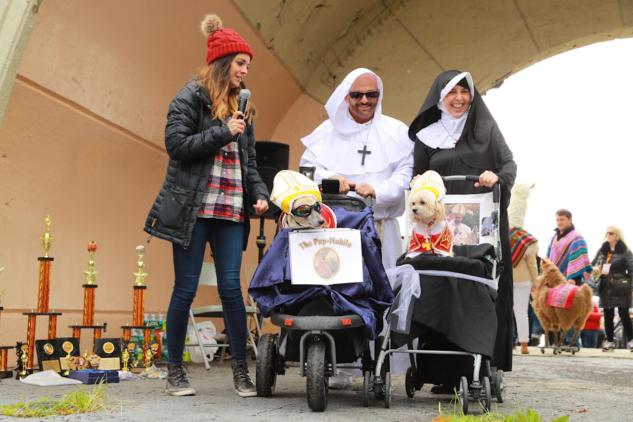 <p>Dogs in carriers dressed as Popes stand on stage before the judges during the 28th Annual Tompkins Square Halloween Dog Parade at East River Park Amphitheater in New York on Oct. 28, 2018. (Photo: Gordon Donovan/Yahoo News) </p>