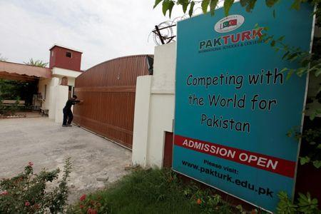 FILE PHOTO - A man closes the main gate of PakTurk International Schools and Colleges in Islamabad