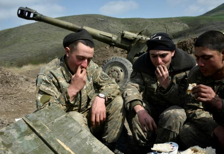 Soldiers of the defense army of Nagorny Karabakh eat by their gun at an artillery position outside the village of Mataghis