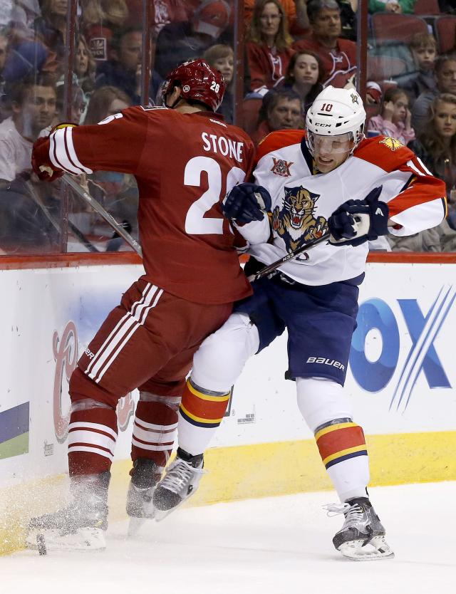 Florida Panthers' Joey Crabb (10) checks Phoenix Coyotes' Michael Stone (26) into the boards as both go for the puck during the first period of an NHL hockey game, Thursday, March 20, 2014, in Glendale, Ariz. (AP Photo/Ross D. Franklin)