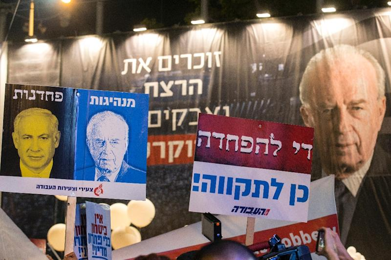 """Demonstrators hold posters bearing the image of Israeli Prime Minister Benjamin Netanyahu (L) and the word """"cowardice"""" in Hebrew - next to an image of late prime minister Yitzhak Rabin with the word """"leadership"""" in Tel Aviv on October 31, 2015 (AFP Photo/Jack Guez)"""