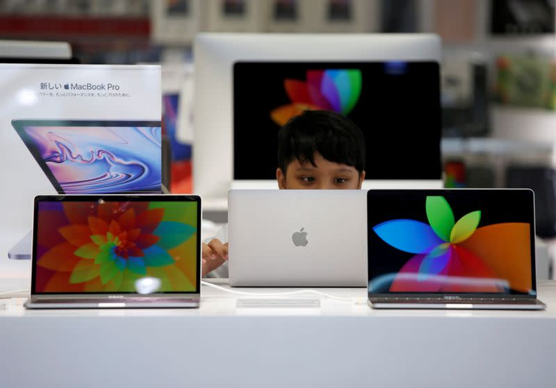 FILE PHOTO: A boy tries to use an Apple laptop at a computer shop in Tokyo