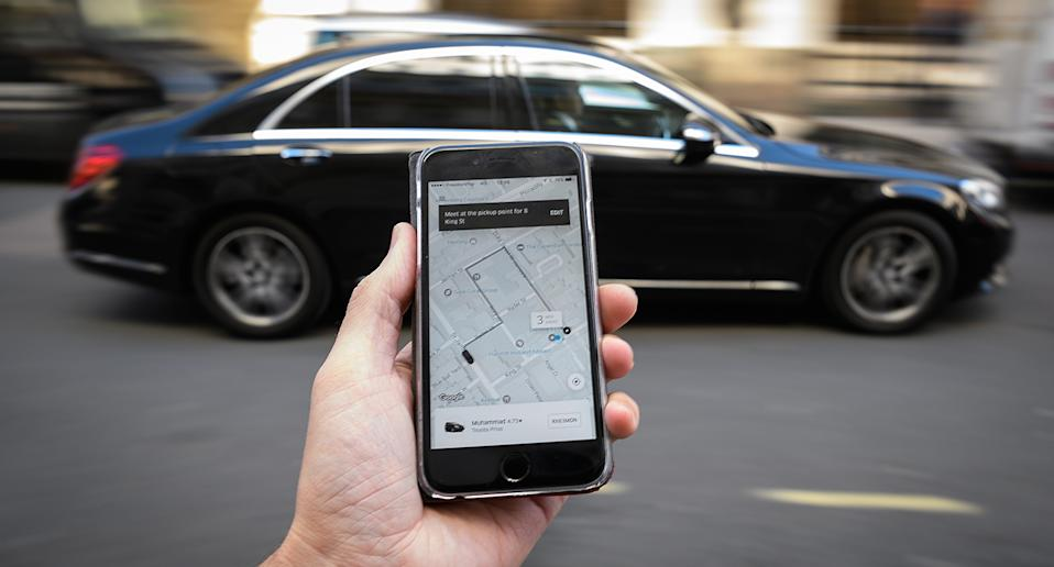 a phone displays the Uber ride-hailing app