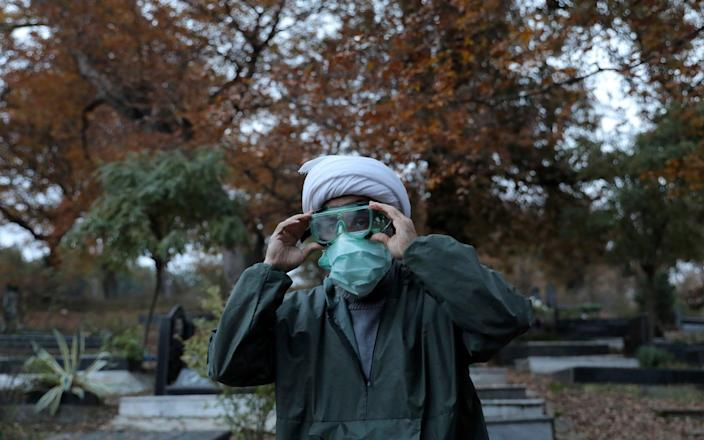Ali Rahimi, 53, a volunteer cleric wearing protective clothing prepares for a funeral - Ebrahim Noroozi