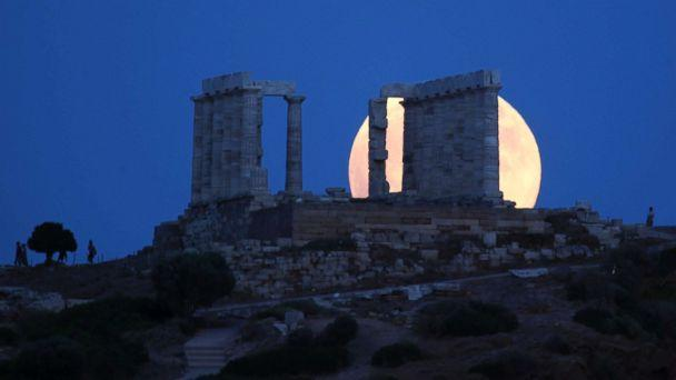 PHOTO: A full moon rises behind the ancient temple of Poseidon in Cape Sounio, south of Athens, July 27, 2018. (Thanassis Stavrakis/AP)