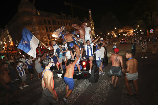 FILE - In this July 16, 2020 file photo, FC Porto fans ride on top of a vehicle while celebrating in downtown Porto, Portugal, after their team beat Sporting CP 2-0 to win the championship. Portugal is taking center stage for soccer during the next two weeks a country where rivalries between clubs go well beyond the field of play. The decisive stages of the Champions League will begin on Wednesday Aug. 12, 2020, in the southern European nation where back-and-forth accusations and legal actions involving the countrys top teams are routine. (AP Photo/Miguel Angelo Pereira, File)