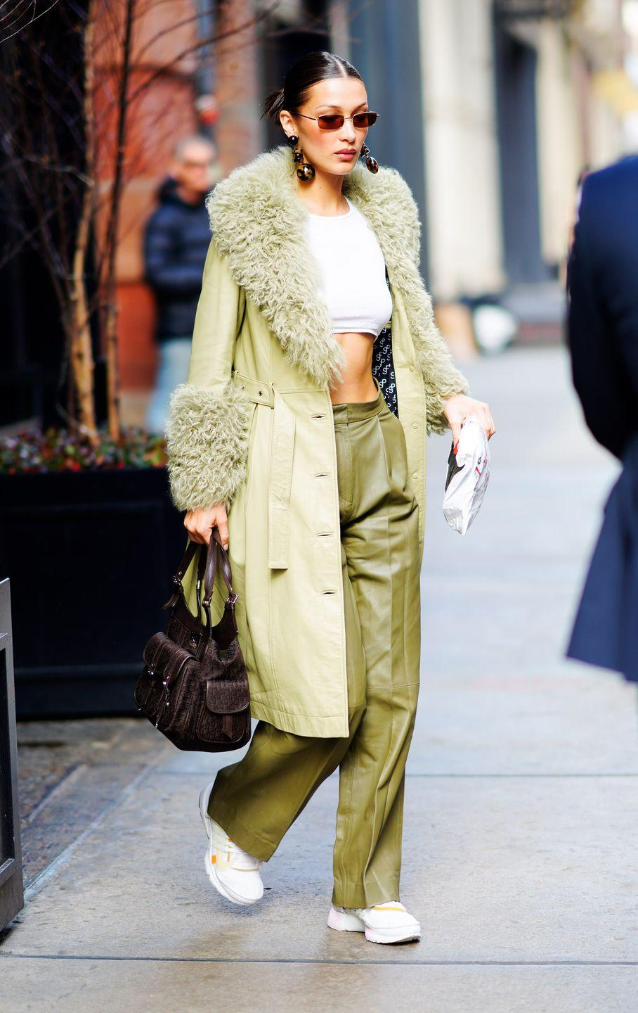 <p>In a pistachio trench coat by Saks Potts, a cropped white top, green slacks, narrow amber shades, brown earrings, a brown handbag, and white sneakers.</p>