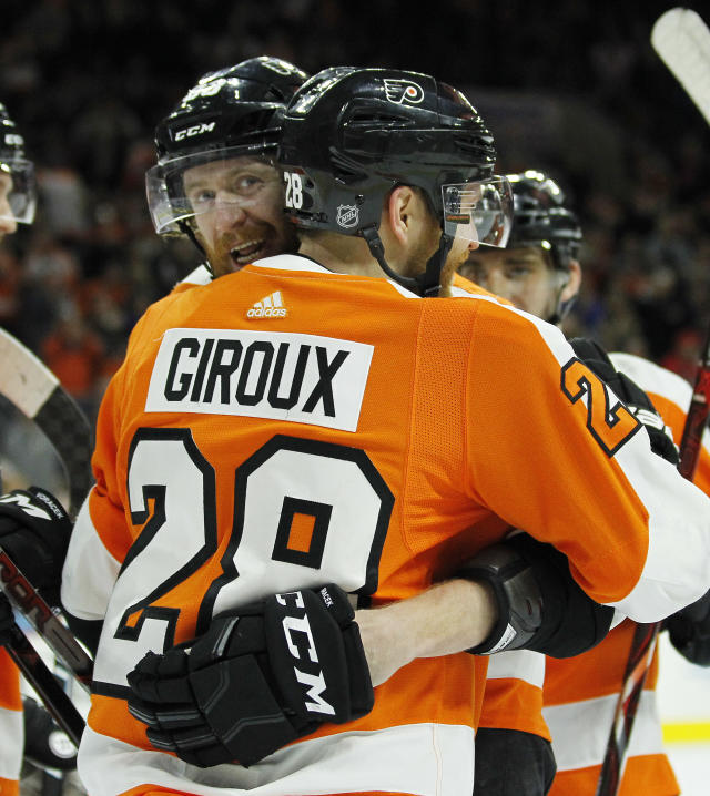 Philadelphia Flyers' Jakub Voracek, facing, hugs Claude Giroux after Giroux's goal during the second period of an NHL hockey game against the New York Rangers, Saturday, April 7, 2018 in Philadelphia, PA. (AP Photo/Tom Mihalek)