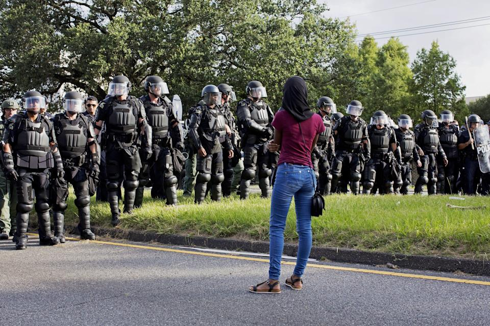 A protester watches as police in riot gear clear the street of protesters in front of the Baton Rouge Police Department headquarters in Baton Rouge, La., Saturday, July 9, 2016. (AP Photo/Max Becherer)