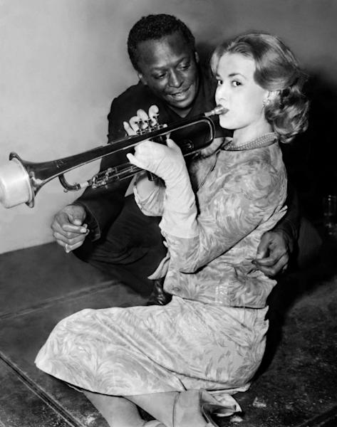 "US trumpet player Miles Davis gives a trumpet lesson to French actress Jeanne Moreau in Paris in December 1957; the jazz legend was the subject of a 2015 biopic film ""Miles Ahead,"" directed by actor Don Cheadle donne une leçon de trompette à l'actrice française Jeanne Moreau, le 05 décembre 1957 à Paris. Miles Davis a été sollicité par le réalisateur Louis Malle pour improviser une musique d'accompagnement de son film ""Ascenseur pour l'échafaud, dans lequel Jeanne Moreau est une des vedettes principales. US trumpet player Miles Davis gives a lesson to French actress Jeanne Moreau in Paris 05 December 1957. Davis was asked by French director Louis Malle to improvise a music for his film ""Elevator to the Gallows"" in which Jeanne Moreau plays"