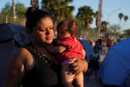 "A Honduran asylum seeker carries her daughter in an encampment where they live near the Gateway International Bridge after being sent back under the ""Remain in Mexico"" program in Matamoros."