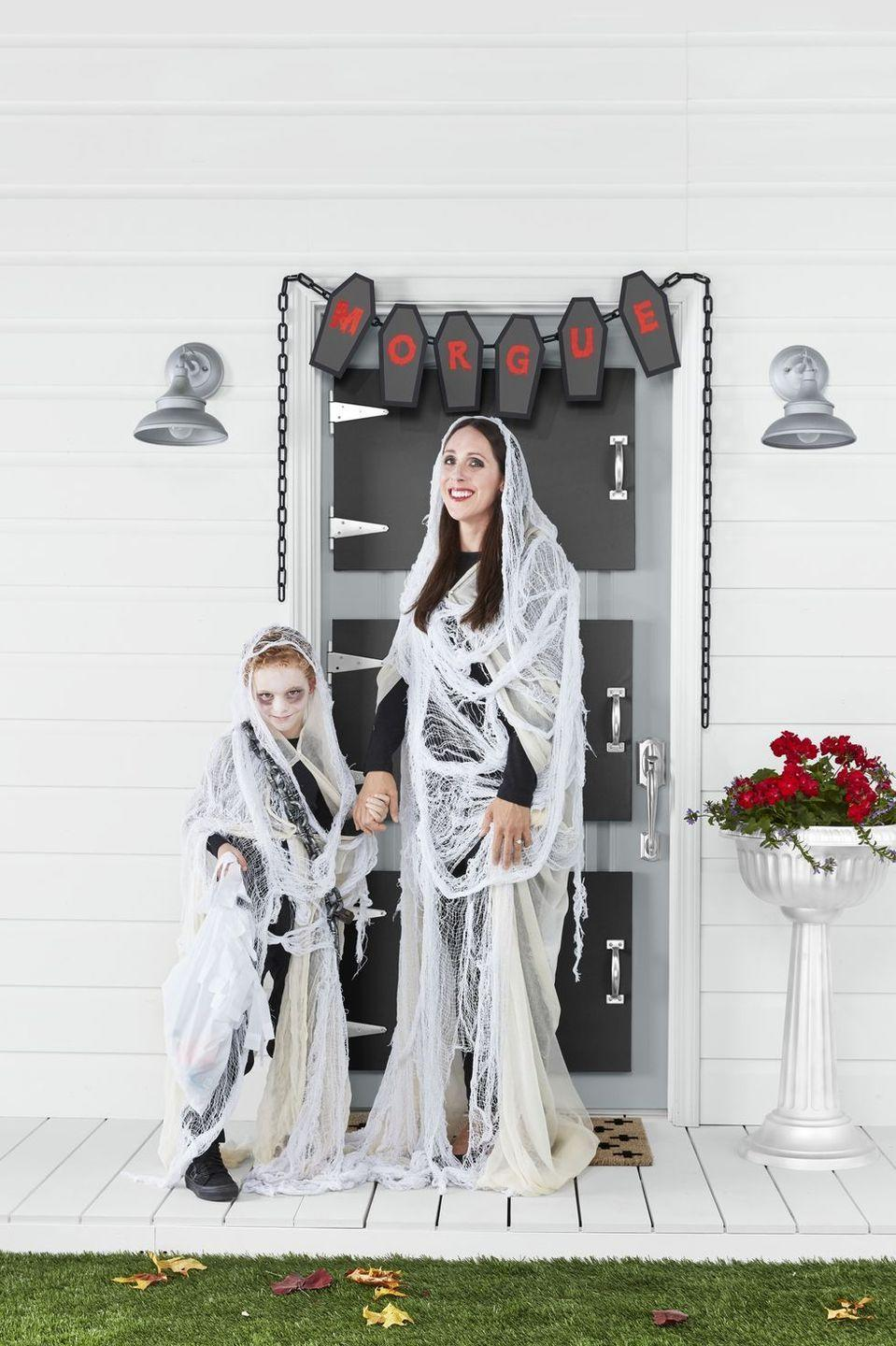 """<p>Got cheesecloth and some black eyeshadow? You're halfway to creating these gauzy ghost costumes, which are just the right mix of """"scary"""" and """"friendly"""" to appeal to both kids and their parents. </p><p><strong>Make the Ghost Costumes: </strong>Start with a base layer of black clothing. Paint face with <a href=""""https://www.amazon.com/Snazaroo-Classic-Face-Paint-White/dp/B000H6W2GW?tag=syn-yahoo-20&ascsubtag=%5Bartid%7C10050.g.23785711%5Bsrc%7Cyahoo-us"""" rel=""""nofollow noopener"""" target=""""_blank"""" data-ylk=""""slk:white face paint"""" class=""""link rapid-noclick-resp"""">white face paint</a> and add <a href=""""https://www.amazon.com/Alima-Pure-Satin-Matte-Eyeshadow/dp/B07F7DQ1Q8?tag=syn-yahoo-20&ascsubtag=%5Bartid%7C10050.g.23785711%5Bsrc%7Cyahoo-us"""" rel=""""nofollow noopener"""" target=""""_blank"""" data-ylk=""""slk:black eyeshadow"""" class=""""link rapid-noclick-resp"""">black eyeshadow</a> around the eyes. Drape and pin neutral cheesecloth, holding it in place with white safety pins and allowing it to trail on the floor a bit. Add a second layer of large, loosely woven, white gauze—we used door and window decorating material. Drape a plastic chain and vintage-inspired lock around the shoulders.</p><p><a class=""""link rapid-noclick-resp"""" href=""""https://www.amazon.com/Good-Cook-Cheesecloth-cotton-White/dp/B000BQKCF6?tag=syn-yahoo-20&ascsubtag=%5Bartid%7C10050.g.23785711%5Bsrc%7Cyahoo-us"""" rel=""""nofollow noopener"""" target=""""_blank"""" data-ylk=""""slk:SHOP CHEESECLOTH"""">SHOP CHEESECLOTH</a></p>"""
