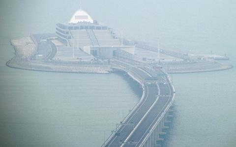 Cars park on a section of the Hong Kong-Zhuhai-Macau Bridge in front of the East Artificial Island in Hong Kong on October 23 - Credit: ANTHONY WALLACE/ AFP