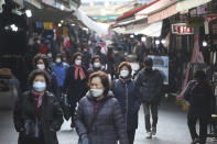 People wearing face masks as a precaution against the coronavirus walk through a market in Seoul, South Korea, Friday, Nov. 27, 2020. South Korea's daily virus tally hovered above 500 for the second straight day, as the country's prime minister urged the public to stay home this weekend to contain a viral resurgence. (AP Photo/Ahn Young-joon)