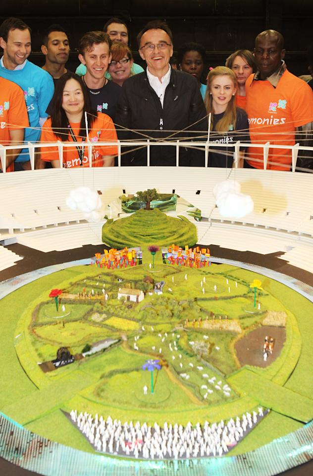 LONDON, UNITED KINGDOM - JUNE 12:  In this handout image provided by LOCOG, artistic director Danny Boyle poses with volunteers next to a model of the London 2012 Olympic Games opening ceremony on June 12, 2012 in London, England.  (Photo by Dave Poultney/LOCOG via Getty Images)