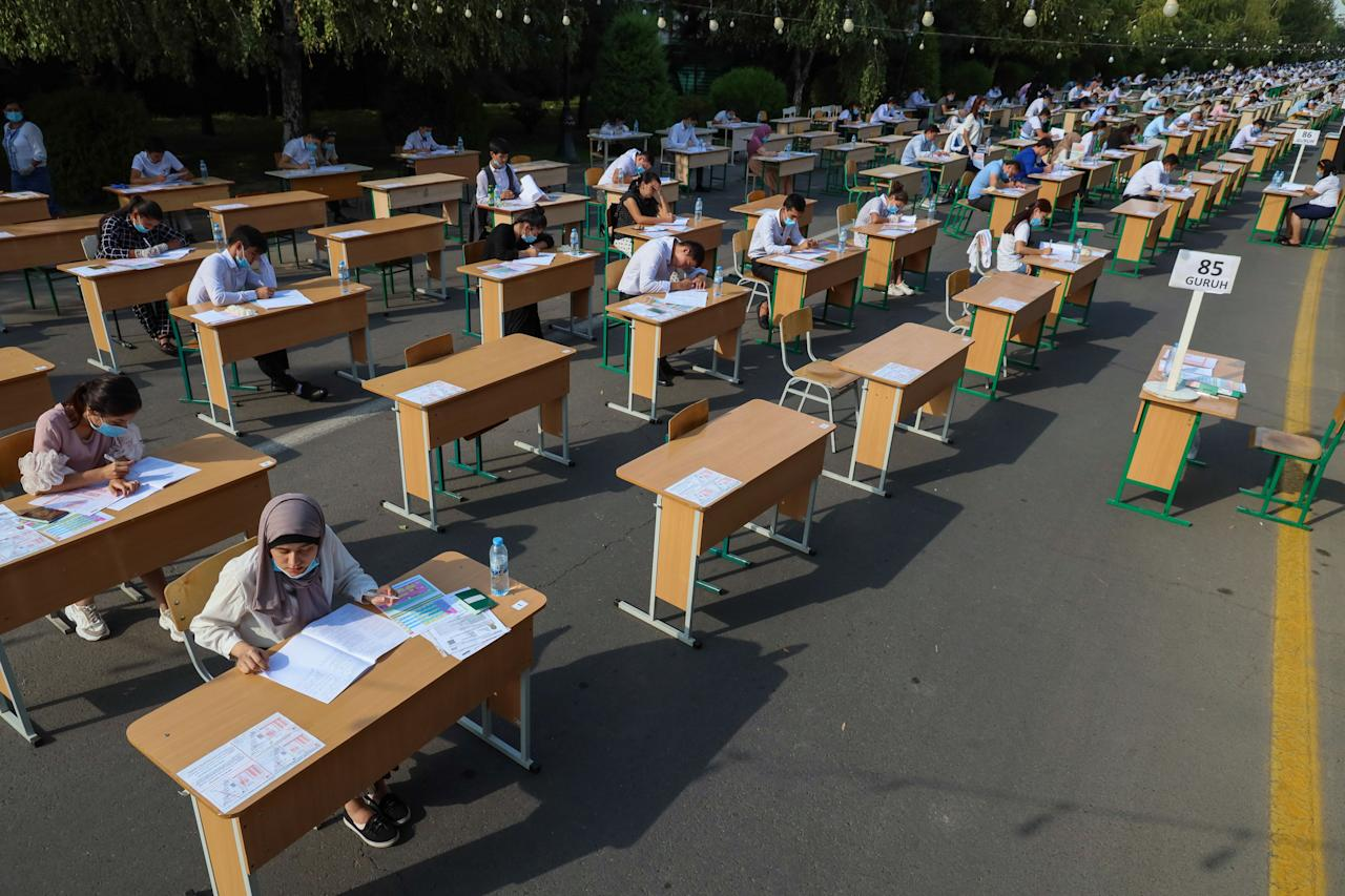 Varios estudiantes uzbekos realizan un examen en plena calle en la capital Taskent. (Photo by YURI KORSUNTSEV/AFP via Getty Images)
