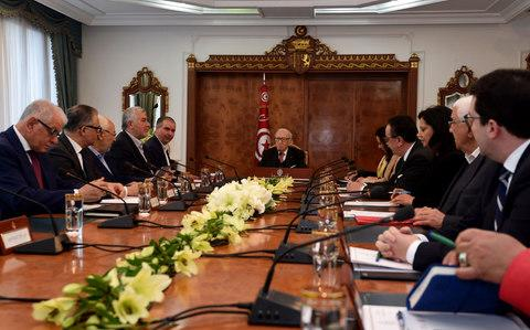 Tunisian President Beji Caid Essebsi (C) attends a meeting with political parties, unions and employers following unrest triggered by austerity measures - Credit: FETHI BELAID/AFP