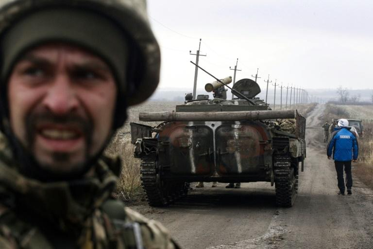An observer of the Organisation for Security and Co-operation in Europe looks at a tank as the OSCE monitors the withdrawal of the Ukrainian forces near Bogdanivka village in the Donetsk region, on November 9, 2019 (AFP Photo/-)