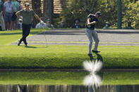 Phil Mickelson tries to skip a ball onto the 16th green as Viktor Hovland, of Norway, looks on during a practice round for the Masters golf tournament on Tuesday, April 6, 2021, in Augusta, Ga. (AP Photo/Matt Slocum)