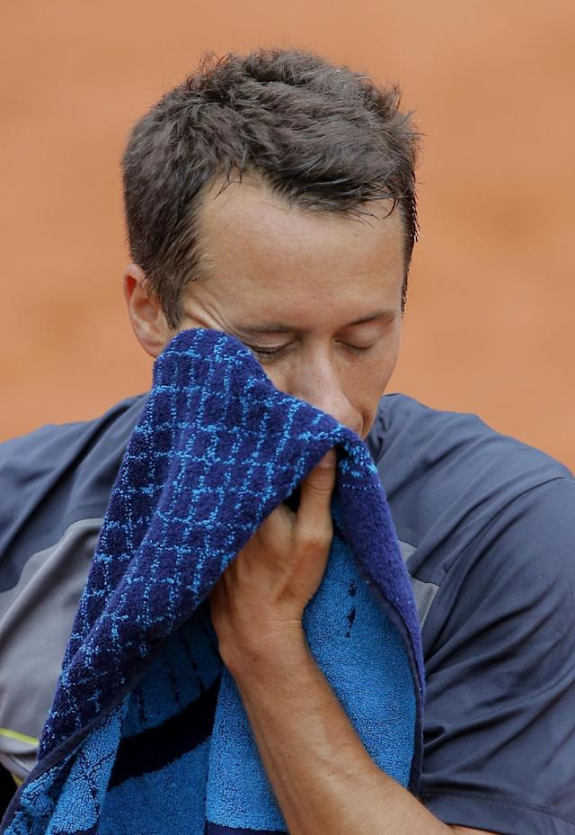 Germany's Philipp Kohlschreiber wipes his face as he plays Britain's Andy Murray during their third round match of the French Open tennis tournament at the Roland Garros stadium, in Paris, France, Sunday, June 1, 2014. Murray won 3-6, 6-3, 6-3, 4-6, 12-10. (AP Photo/Michel Spingler)